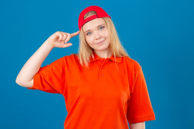 Jeune femme de livraison portant un polo orange et une casquette rouge pointant le temple avec la pensée du doigt axée sur une tâche sur fond bleu isolé