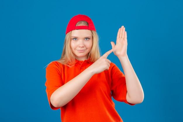 Jeune femme de livraison portant un polo orange et une casquette rouge pointant vers la main ouverte de pal regardant la caméra avec le sourire sur le visage sur fond bleu isolé