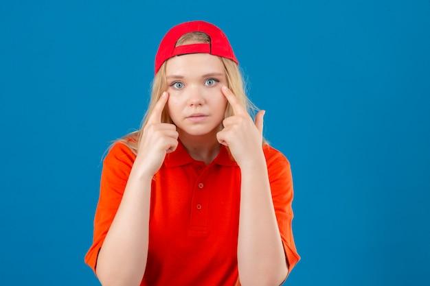 Jeune femme de livraison portant un polo orange et une casquette rouge regardant la caméra en pointant ses yeux sur fond bleu isolé