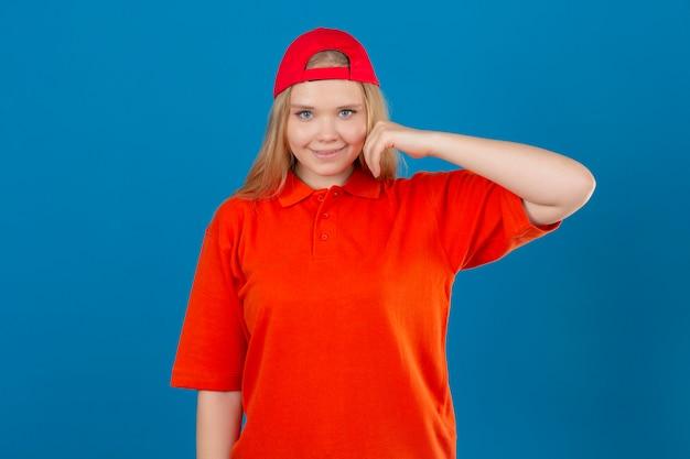 Jeune femme de livraison portant un polo orange et une casquette rouge souriant joyeusement touchant la joue sur fond bleu isolé