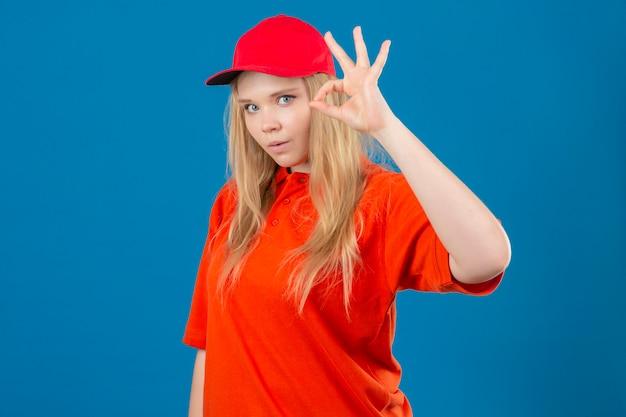 Jeune femme de livraison portant un polo orange et une casquette rouge à la surprise de faire signe ok sur fond bleu isolé
