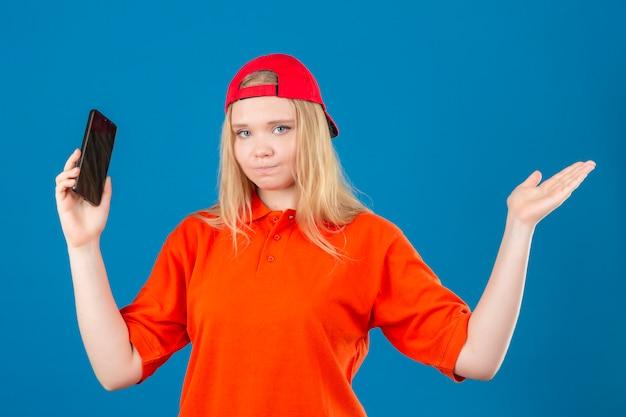 Jeune femme de livraison portant un polo orange et une casquette rouge tenant le smartphone en haussant les épaules et les yeux ouverts confus sur fond bleu isolé