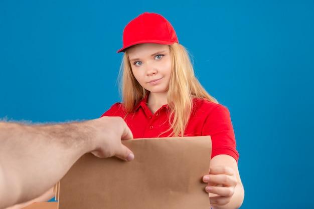 Jeune femme de livraison portant un polo rouge et une casquette donnant un paquet de papier à un client à la confiance sur fond bleu isolé