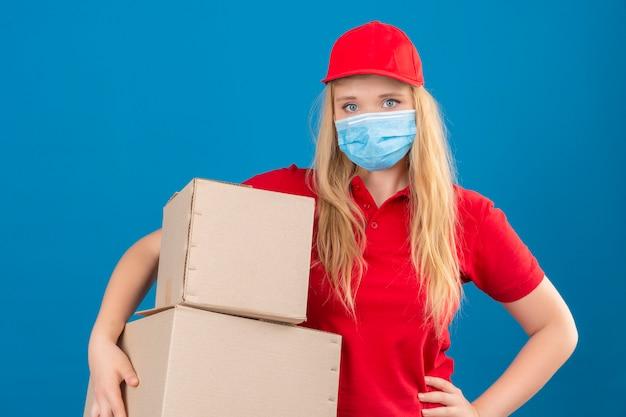 Jeune femme de livraison portant un polo rouge et une casquette en masque de protection médicale debout avec des boîtes en carton à la fatigue et surmené sur fond bleu isolé