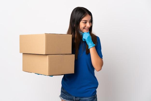 Jeune femme de livraison protégeant du coronavirus avec un masque isolé sur un mur blanc en pensant à une idée et en regardant le côté