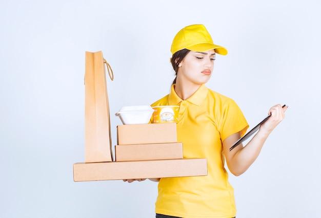 Jeune femme de livraison regardant la liste de contrôle
