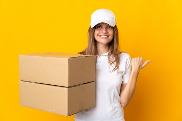 Jeune femme de livraison slovaque isolée sur un mur jaune pointant vers le côté pour présenter un produit