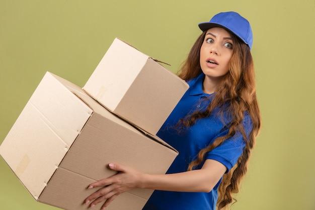 Jeune femme de livraison tendue aux cheveux bouclés portant un polo bleu et une casquette avec des boîtes à la surprise sur fond vert isolé