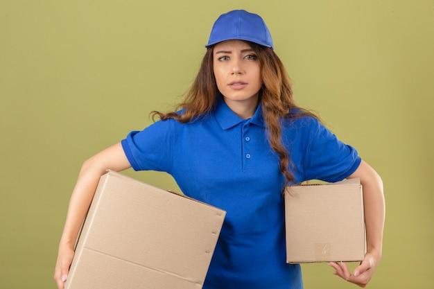 Jeune femme de livraison tendue aux cheveux bouclés portant un polo bleu et une casquette debout avec des boîtes à la fatigue sur fond vert isolé
