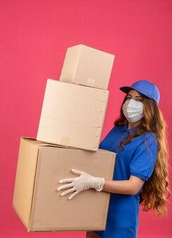 Jeune femme de livraison tendue aux cheveux bouclés portant un polo bleu et une casquette en masque de protection médicale debout avec des boîtes sur fond rose isolé