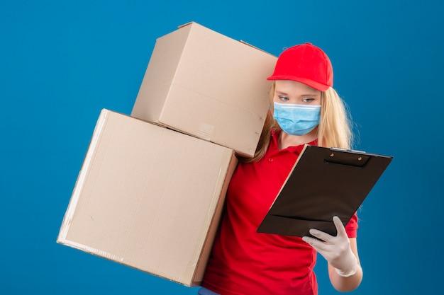 Jeune femme de livraison tendue portant un polo rouge et une casquette en masque de protection médicale debout avec des boîtes en carton tout en tenant le presse-papiers dans l'autre main en le regardant sur bleu isolé