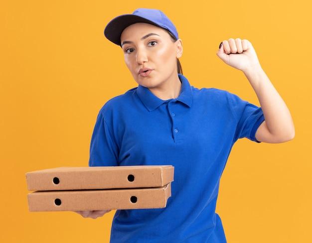 Jeune femme de livraison en uniforme bleu et cap tenant des boîtes de pizza à l'avant avec une expression confiante levant le poing debout sur le mur orange
