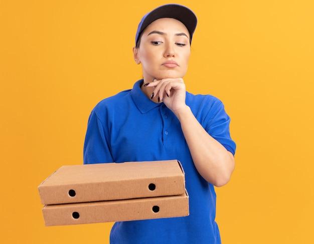 Jeune femme de livraison en uniforme bleu et cap tenant des boîtes de pizza en les regardant avec une expression pensive sur le visage pensant debout sur un mur orange