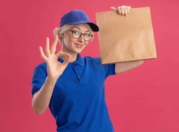 Jeune femme de livraison en uniforme bleu et casquette portant des lunettes tenant un paquet de papier souriant joyeusement montrant ok chanter sur mur rose
