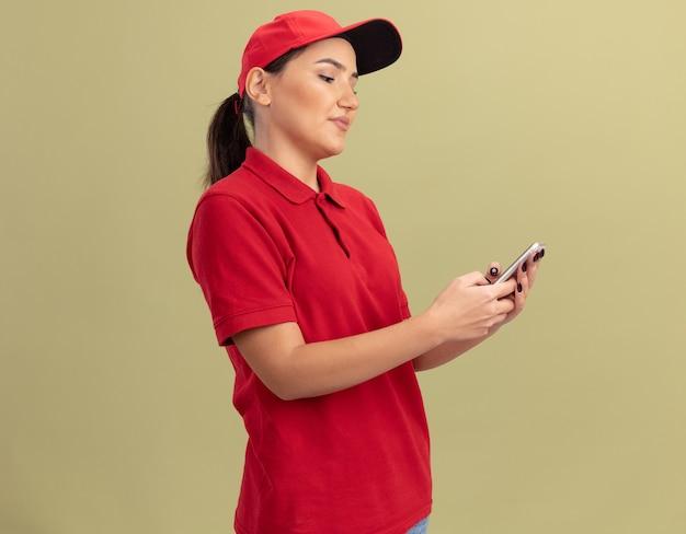 Jeune femme de livraison en uniforme rouge et cap à l'aide de smartphone en le regardant avec le sourire sur le visage debout sur mur vert