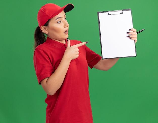 Jeune femme de livraison en uniforme rouge et cap holding presse-papiers avec des pages vierges pointant avec l'index au presse-papiers à la confusion debout sur le mur vert