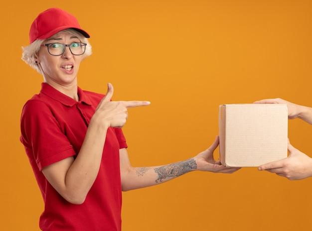 Jeune femme de livraison en uniforme rouge et cap se sentant confus tout en recevant le paquet de boîte pointant avec l'index au fort debout sur le mur orange