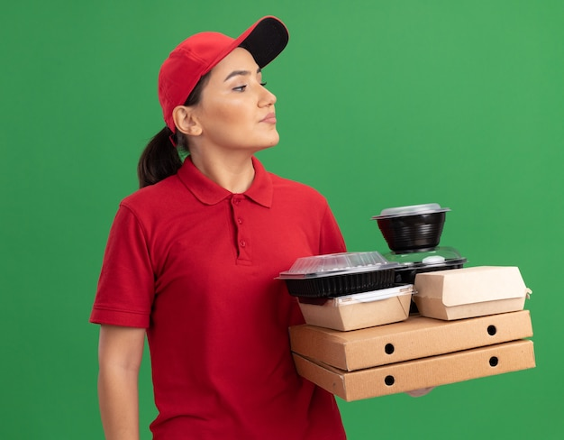 Jeune femme de livraison en uniforme rouge et cap tenant des boîtes de pizza et des emballages alimentaires à côté avec un visage sérieux debout sur un mur vert