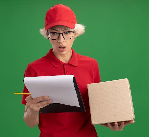 Jeune femme de livraison en uniforme rouge et casquette portant des lunettes avec boîte en carton tenant le presse-papiers avec des pages blanches et un crayon regardant le presse-papiers confus debout sur le mur vert