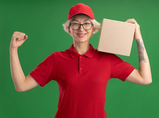 Jeune femme de livraison en uniforme rouge et casquette portant des lunettes tenant une boîte en carton levant le poing souriant confiant à debout sur le mur vert