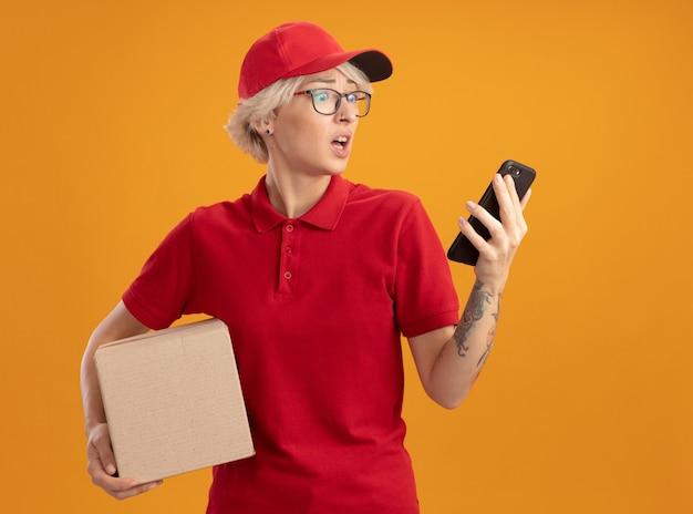 Jeune femme de livraison en uniforme rouge et casquette portant des lunettes tenant une boîte en carton en regardant son smartphone inquiet et confus debout sur un mur orange