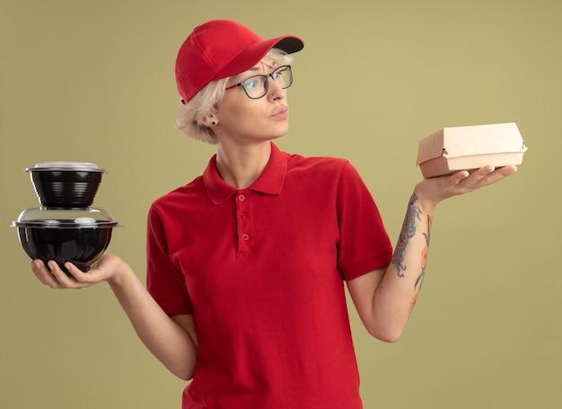 Jeune femme de livraison en uniforme rouge et casquette portant des lunettes tenant des emballages alimentaires à la confusion en essayant de faire un choix debout sur un mur vert
