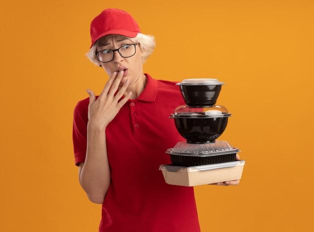 Jeune femme de livraison en uniforme rouge et casquette portant des lunettes tenant pile de colis alimentaires les regardant inquiets et confus debout sur le mur orange