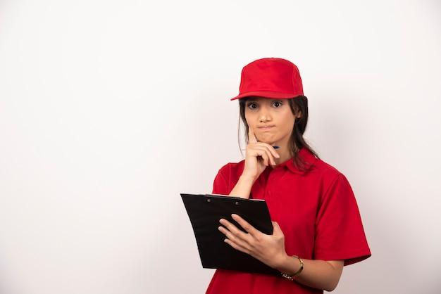Jeune femme de livraison en uniforme rouge avec presse-papiers sur fond blanc.