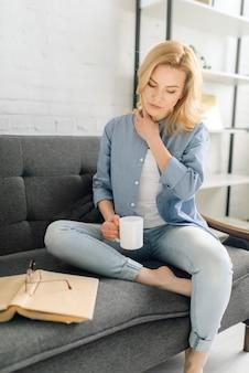 Jeune femme avec livre boit du café sur un canapé noir confortable