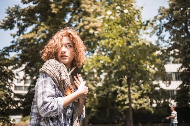 Jeune femme avec un livre dans le parc