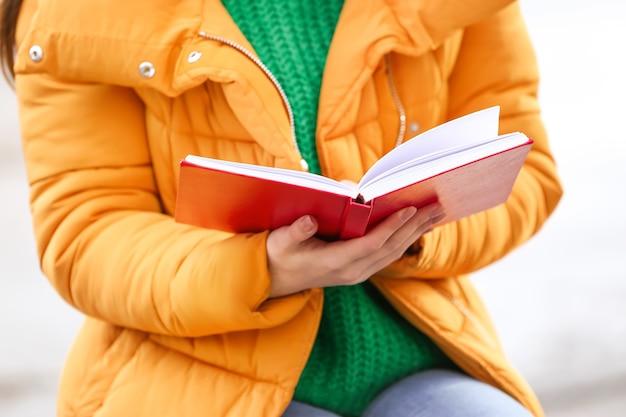 Jeune femme, livre lecture, dehors, gros plan