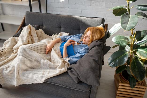 Jeune femme avec livre s'est endormi sous une couverture sur un canapé noir confortable, salon dans des tons blancs