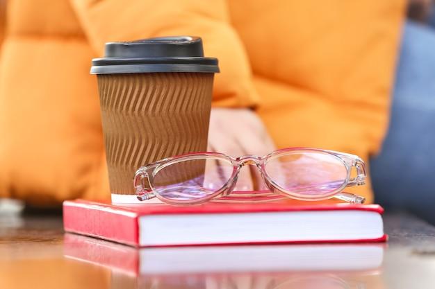 Jeune femme, à, livre, tasse café, et, lunettes, séance banc