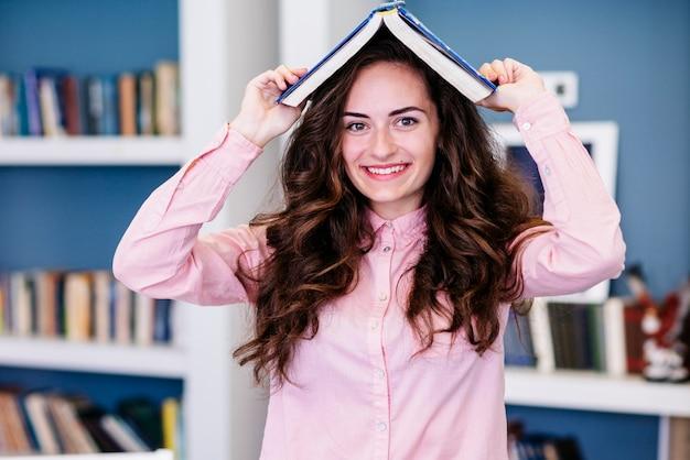 Jeune femme avec un livre sur la tête