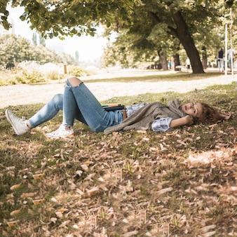 Jeune femme, à, livres, mensonge parc, herbe