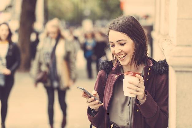 Jeune femme à londres avec thé et téléphone intelligent