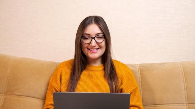 Jeune femme avec de longs cheveux flottants lâches et des lunettes agite la main et parle à la recherche d'un écran d'ordinateur portable gris assis sur un canapé à la maison vue rapprochée