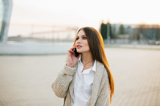 Jeune femme avec de longs cheveux parle au téléphone marchant dehors dans la soirée