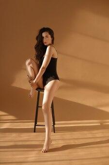 Une jeune femme avec de longues jambes sexy et une forme de corps parfaite dans un body noir posant sur le tabouret sur un mur beige