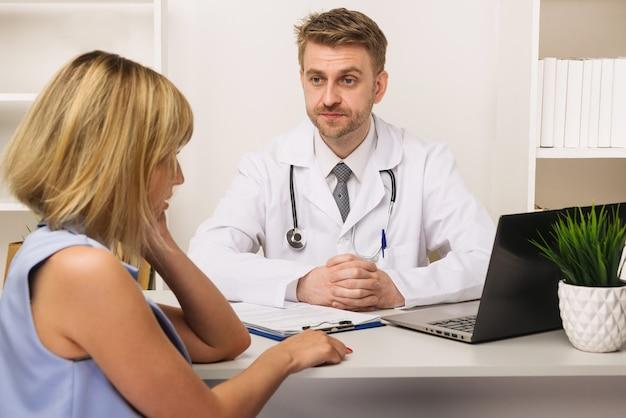 Jeune femme lors d'une consultation avec un chirurgien ou un thérapeute de sexe masculin dans son bureau. mise au point sélective sur le médecin.