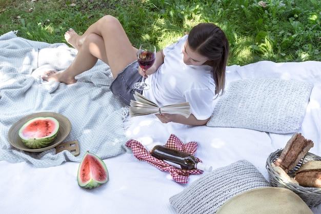 Une jeune femme lors d'un pique-nique en lisant un livre