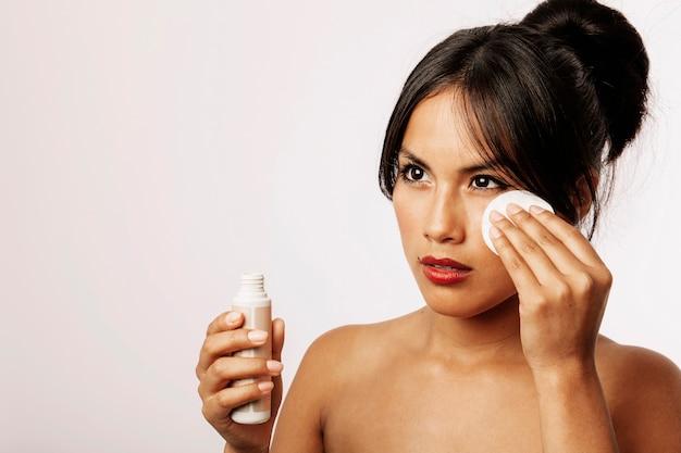 Jeune femme avec lotion cosmétique et coton