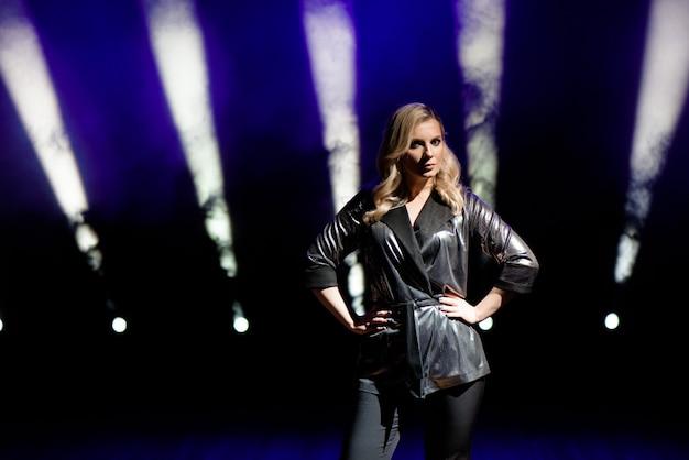 Jeune femme avec des lumières colorées en concert sur la scène.