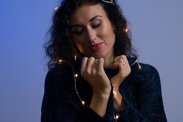 Jeune femme avec les lumières rougeoyantes de noël célébration.