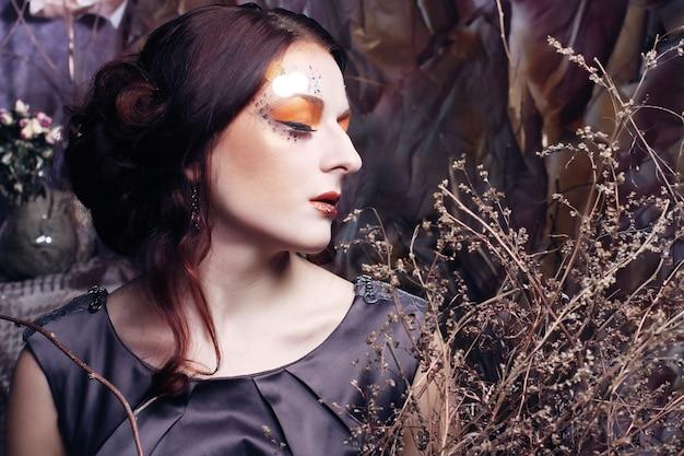 Jeune femme, à, lumineux, maquillage, à, branches sèches