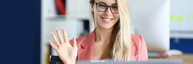 Jeune femme à lunettes en agitant la main à l'écran d'ordinateur portable au bureau