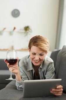 Jeune femme à lunettes allongé sur le canapé à l'aide de tablette numérique et boire du vin rouge dans le verre à vin