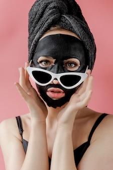 Jeune femme à lunettes appling masque cosmétique en tissu cosmétique noir sur fond rose. masque peeling visage au charbon de bois, soins de beauté spa, soins de la peau, cosmétologie. fermer