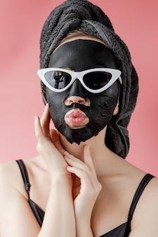 Jeune femme à lunettes appling masque facial en tissu cosmétique noir sur fond rose. masque peeling visage au charbon, soin de beauté spa, soin de la peau, cosmétologie. fermer.