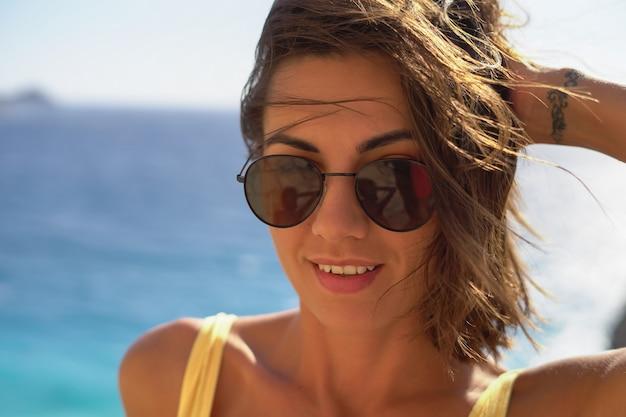 Jeune femme à lunettes de bonne humeur en vacances à la plage profitant d'une chaude journée d'été